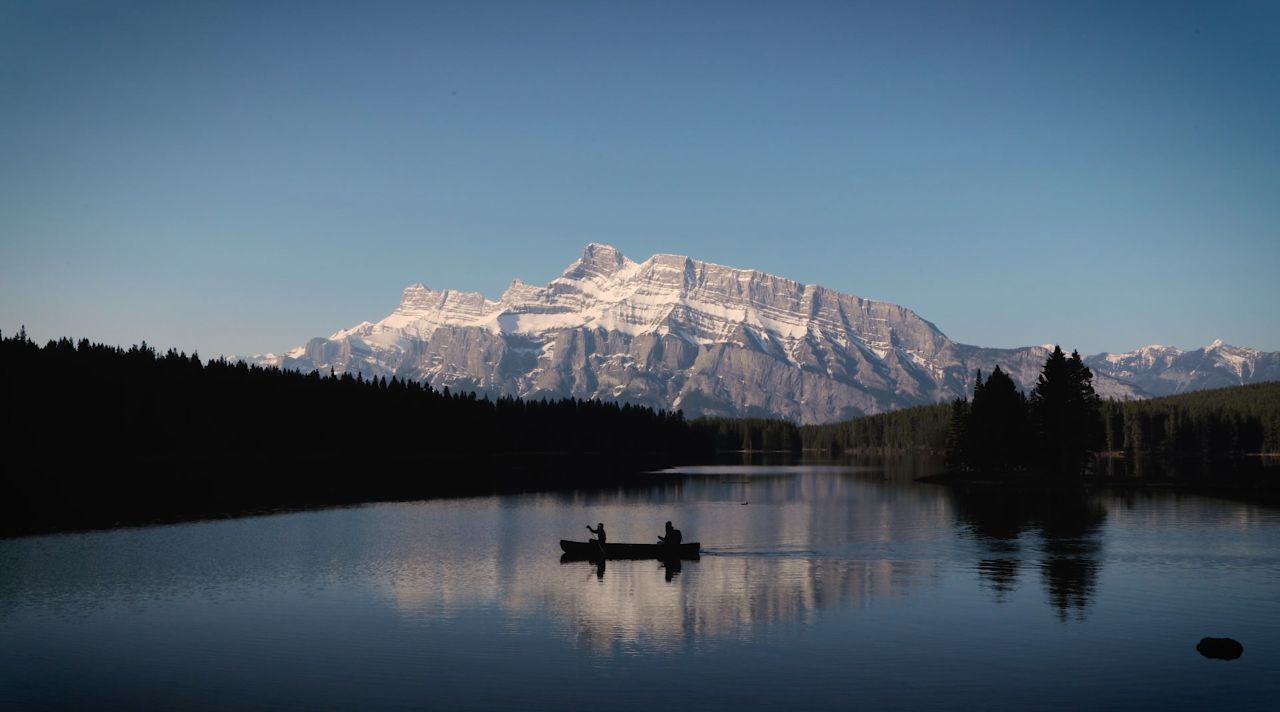 A single canoe on a lake with a mountain range in the background.