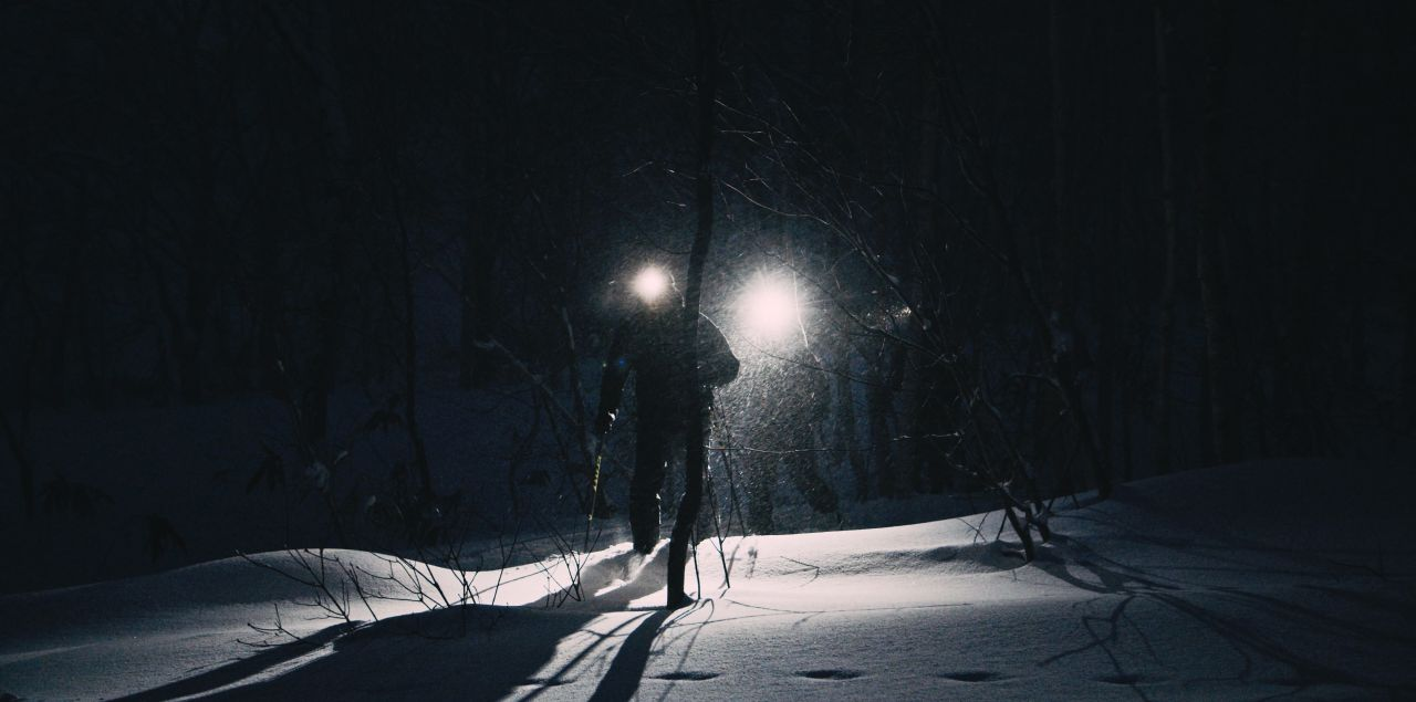 Single light shines through darkness with a man running to camera.