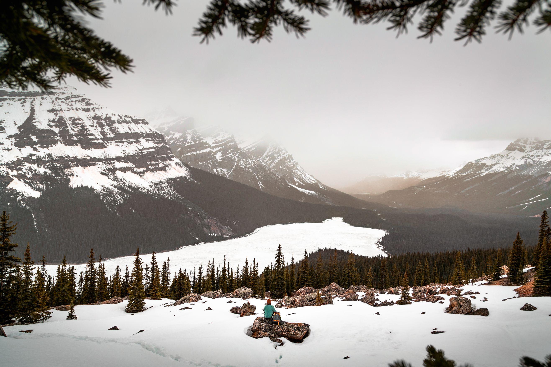 Main sitting on rock overlooking snowy lake.