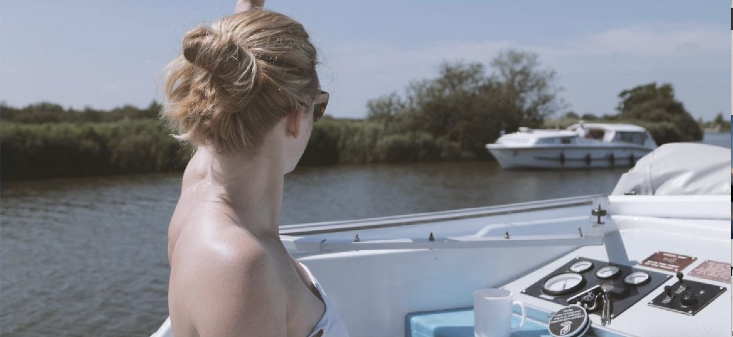 Lady on broad boat looking out over river.