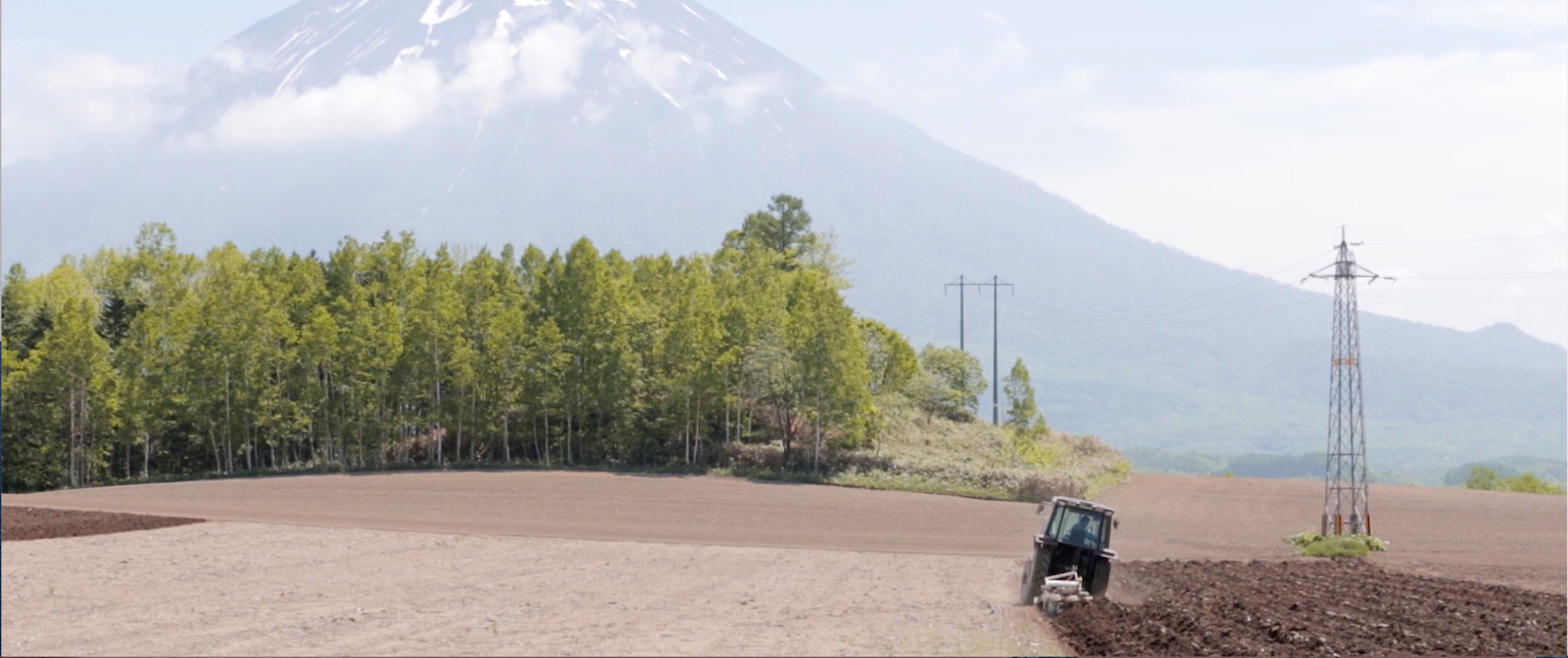 Tractor working on a field with a mountain in the background.