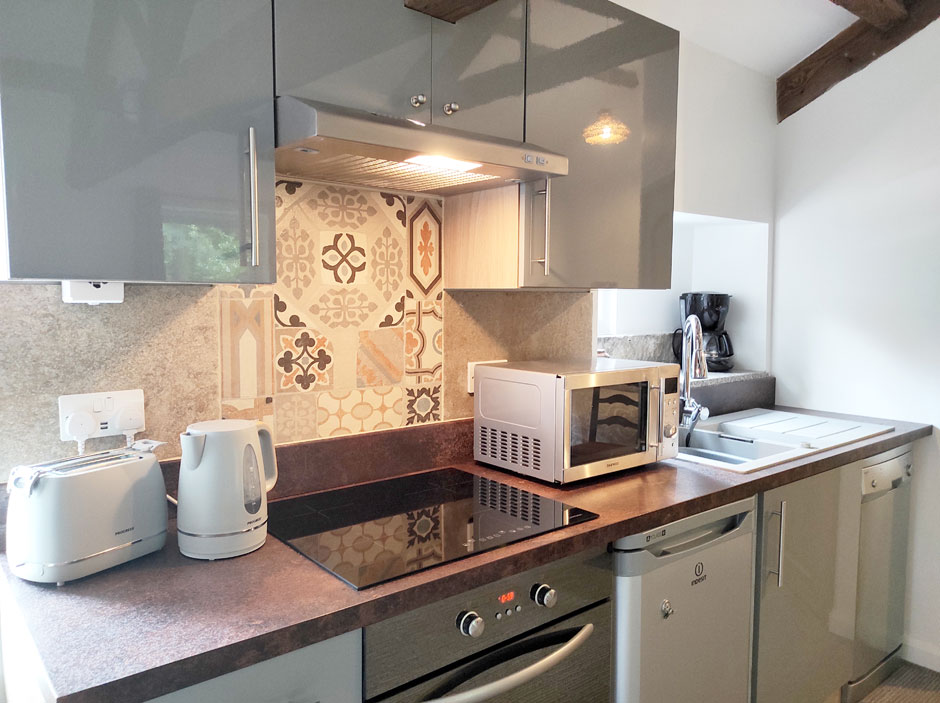 The American-style kitchen upstairs at Headingley Hideaway with glossy grey units, hob, worktop and tiled splashback.