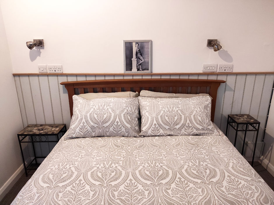The freshly made bed in the upstairs flatlet at Headingley Hideaway, with side tables and wall-mounted reading lamps.