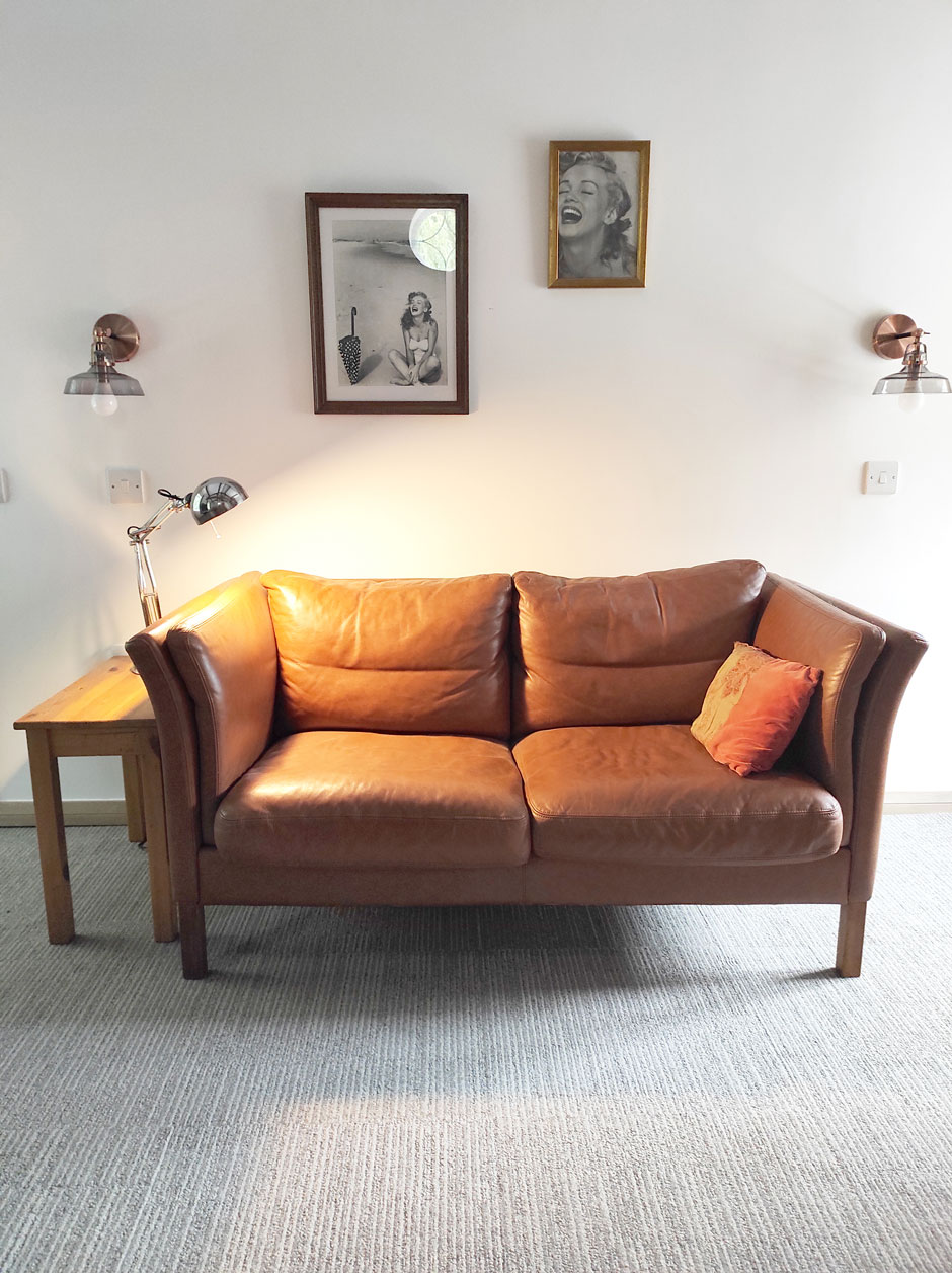 The lounge area of the upstairs flatlet at Headingley Hideaway with grey carpet, a tan leather two-seater sofa and side table with lamp.