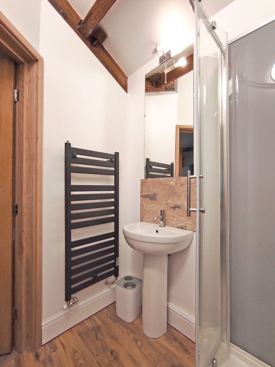 The shower room in the upstairs flatlet at Headingley Hideaway, with a black towel radiator and white ceramic sink.