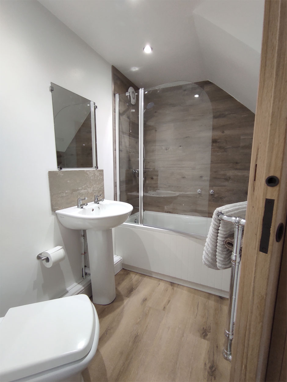 The downstairs flatlet at Headingley Hideaway has a shower over bath and a heated towel rail.