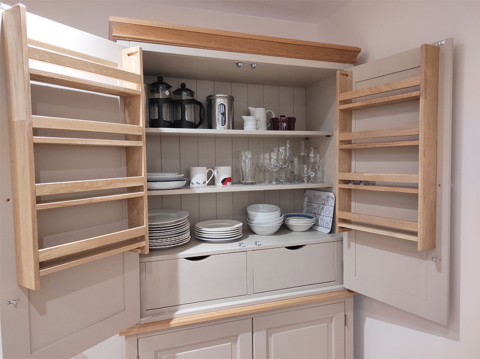 The downstairs flat's wooden larder cupboard with crockery at Headingley Hideaway.