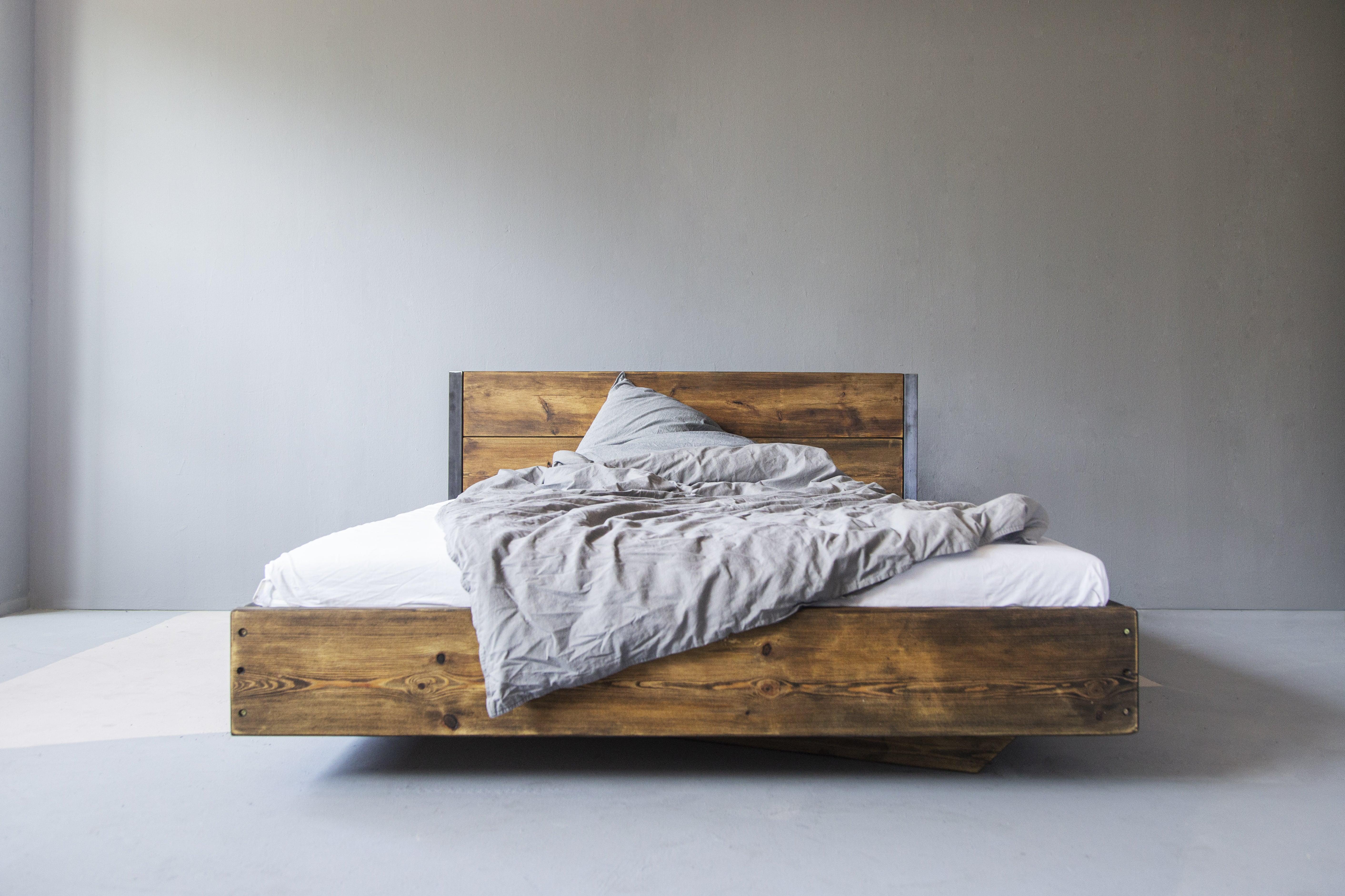 Bett Bauholz Lussa Verdon mit Lehne. Das rustikale Bett aus Bauholz vereint Natur und Handarbeit und zeigt, wie Bauholzdesign heute funktioniert.