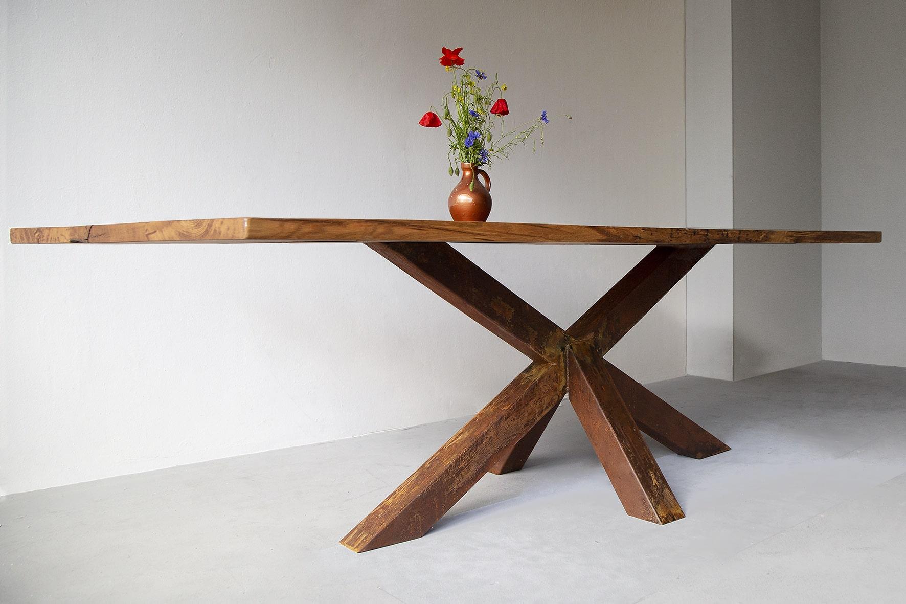 Der Tisch Erika erzählt eine Geschichte von Kontrasten: Massives, kühles Eisen trifft auf warmes und lebendiges Altholz aus Eiche.