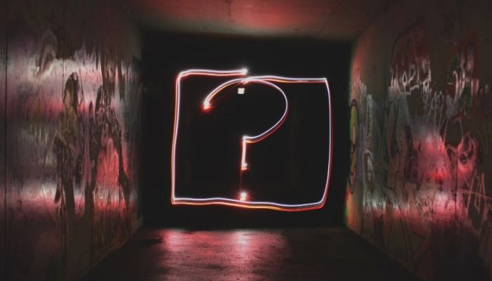A large neon question mark
