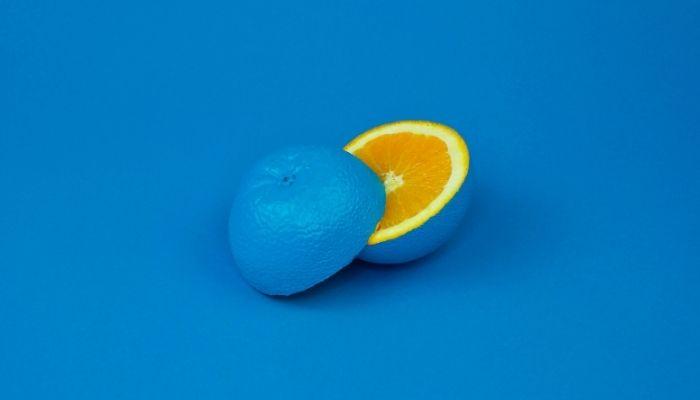 A blue fruit sliced in half, but it's an orange inside