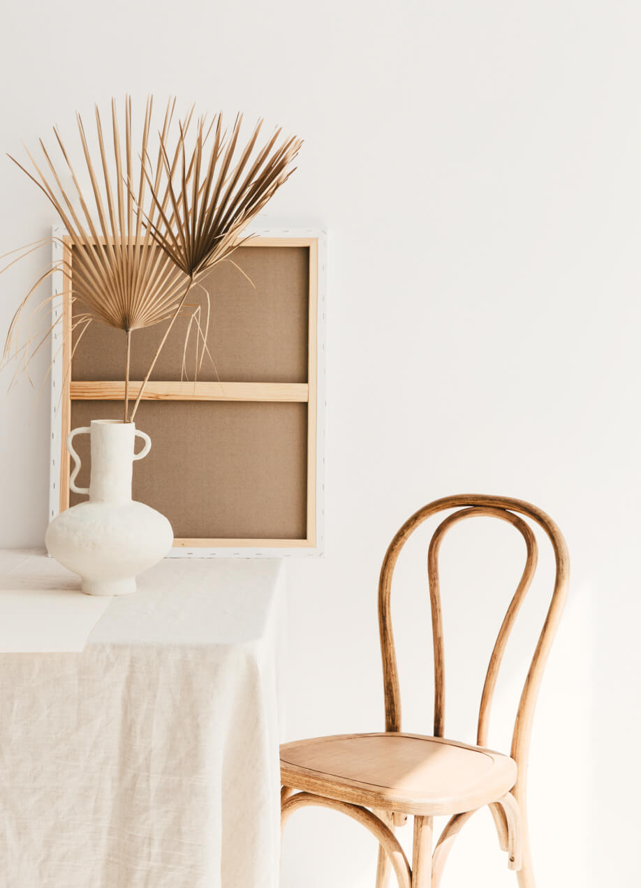Studio image of chair against a table with linen table cloth and artisan vase.