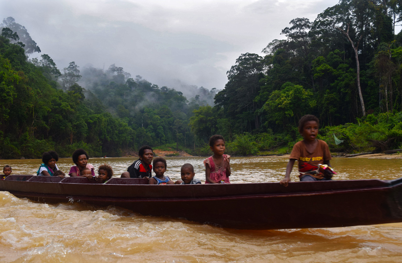 Orang Asli - the indigenous people of the Malay Peninsula sliding down the river in Taman Negara National Park