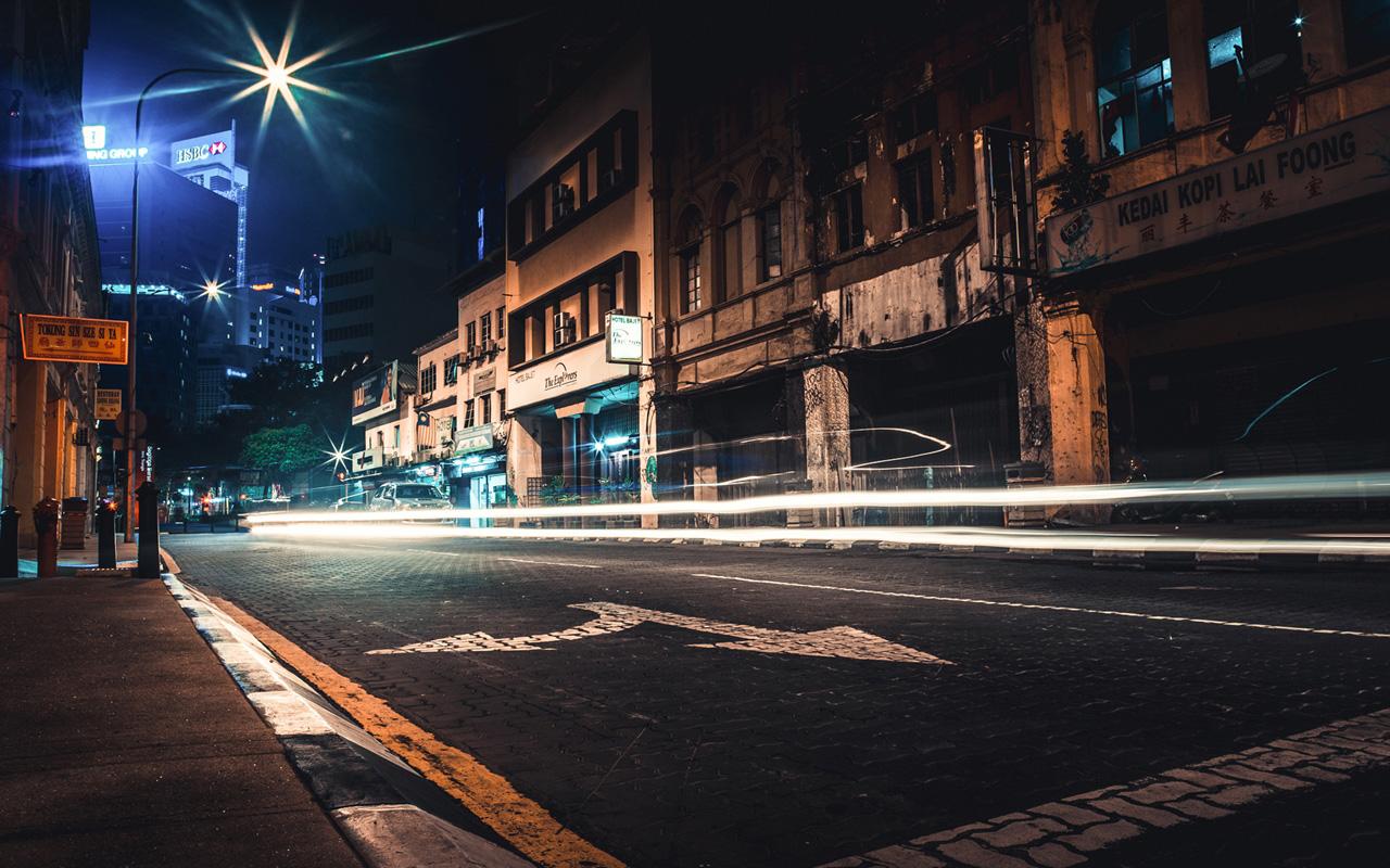 Passing cars light up a street near Old Market, KL.