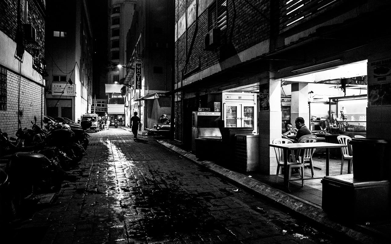 Lone man walking down the street after the night out near Bukit Bintang district in Kuala Lumpur.