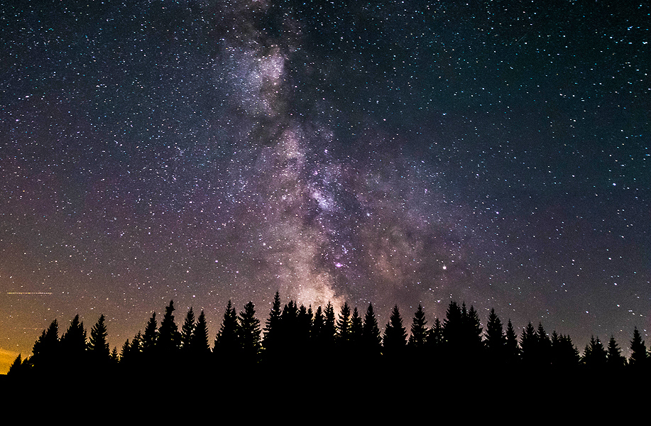 Center of the Milky Way, Saggitarius A glowing immensely above the forests of Sumava