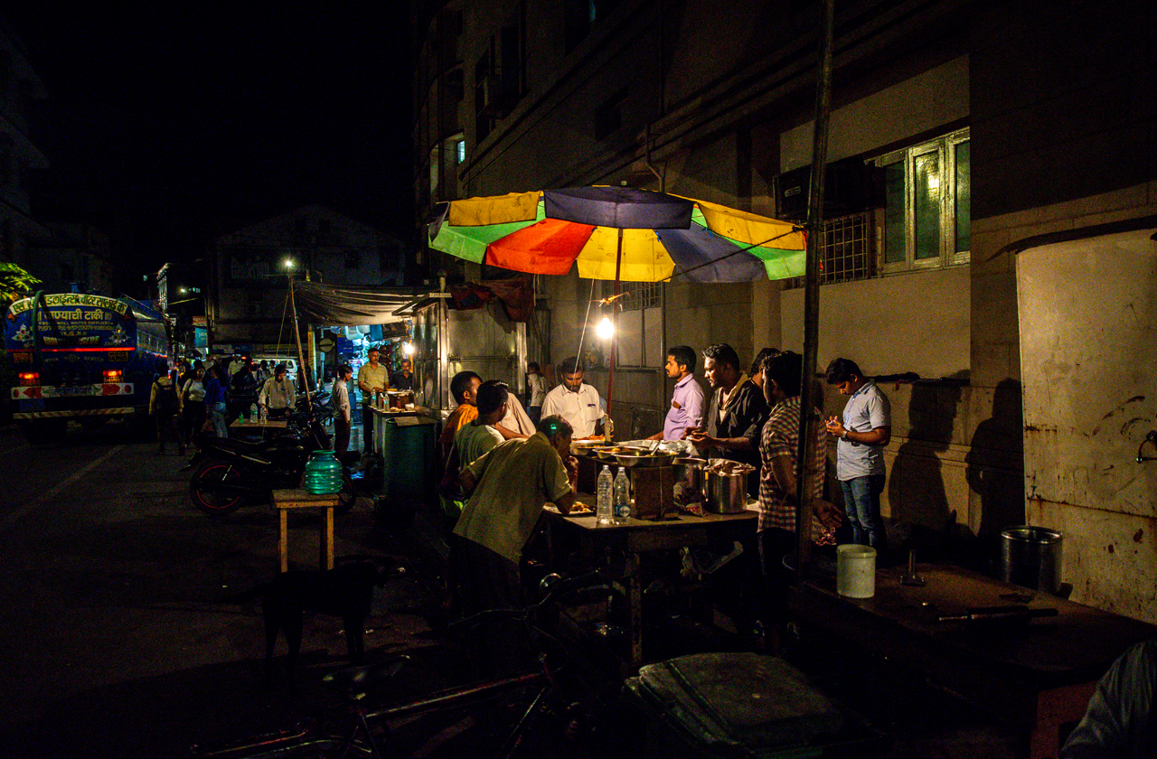 Group of men gathering around a street food stall to chat and eat their dinner.