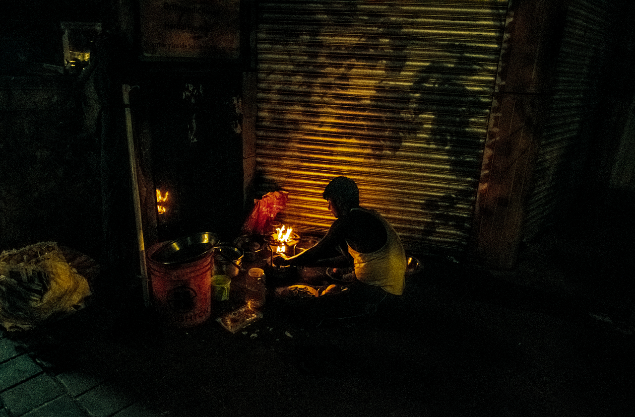 A young man is starting a fire to cook his dinner in a hidden corner near Mohammed Ali Road.