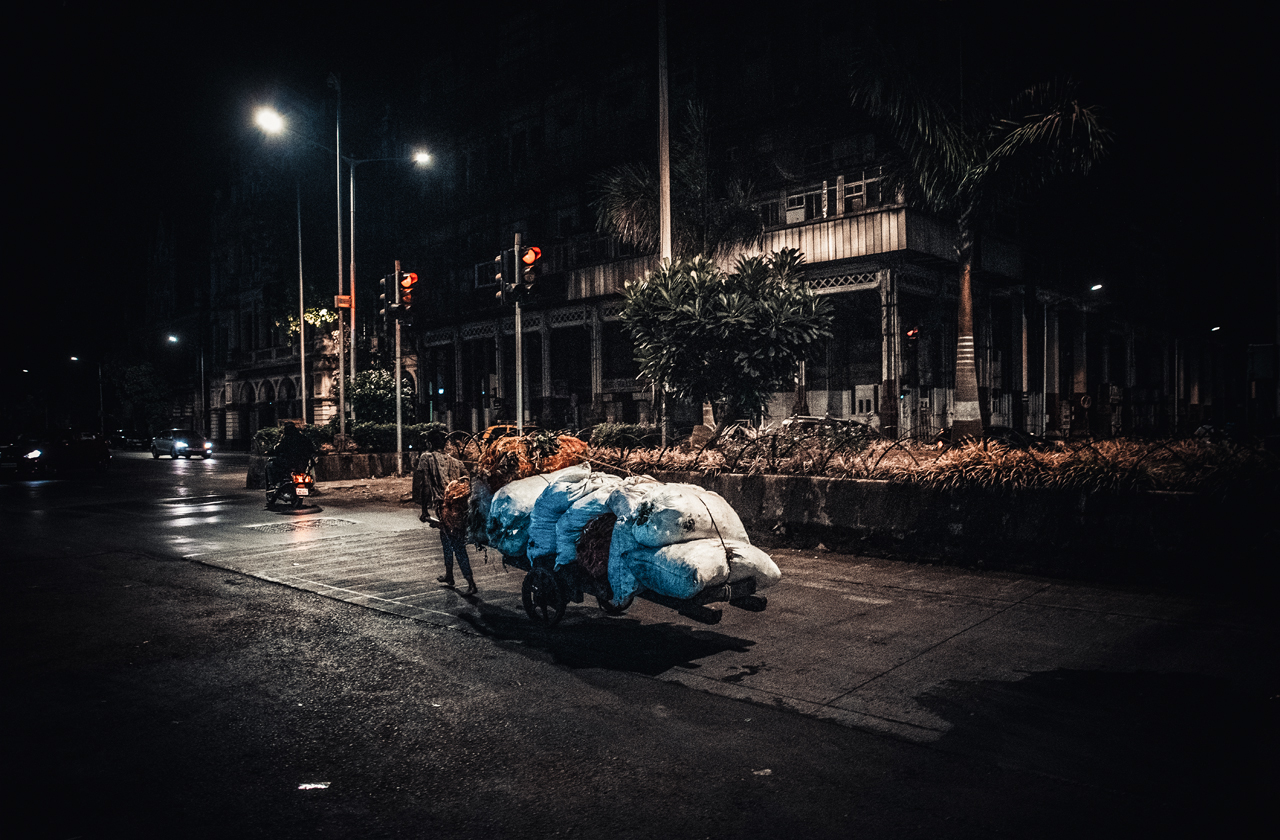 A worker is returning home after a long day. He collected a lot of rubbish, which he will separate into usable and unusable parts and scraps.