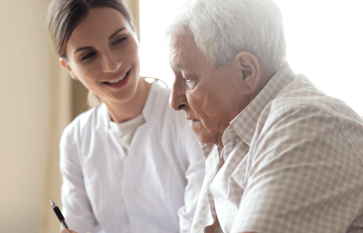 Pflegekraft unterhält sich mit Bewohner