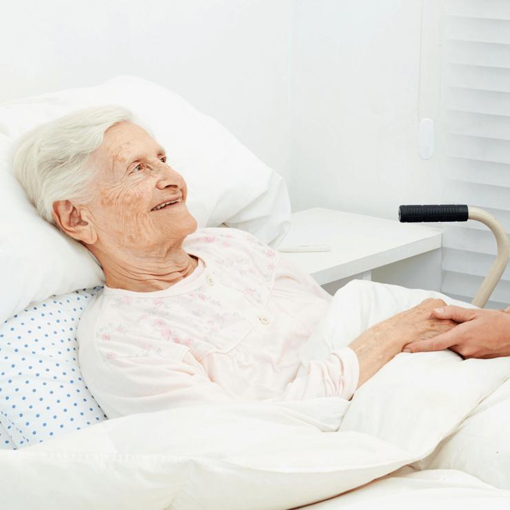 Eine Bewohnerin liegt im Bett und lächelt