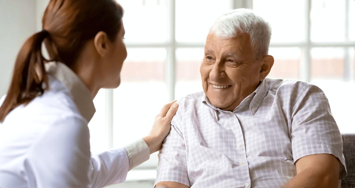 Eine Altenpflegerin spricht mit einem Bewohner und berührt ihn dabei an der Schulter.