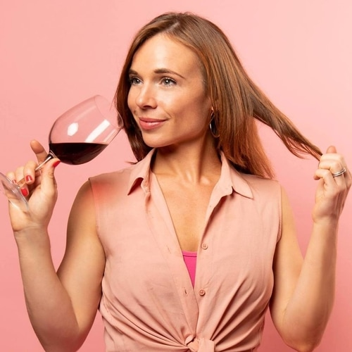 Woman drinking glass of red wine while playing with brown hair