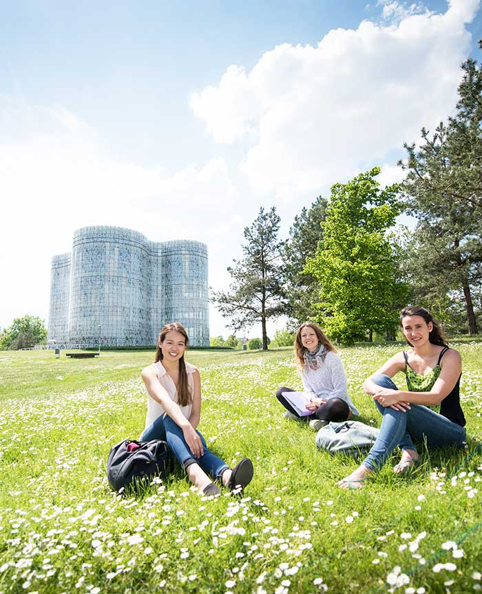 a group of girls sitting in a meadow on campus