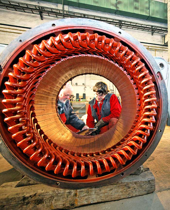 two men working behind a turbine