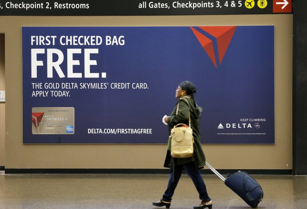 """Someone walking in front of a """"first checked bag"""" ad from Delta"""