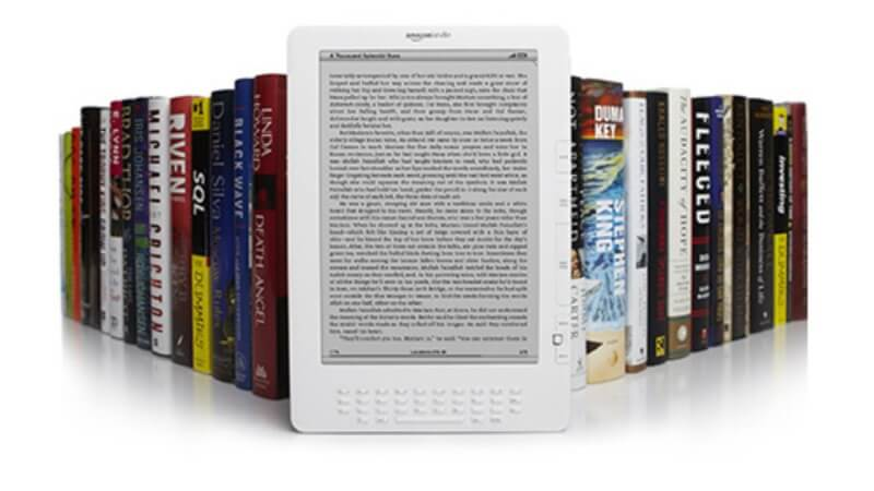 A Kindle surrounded by books