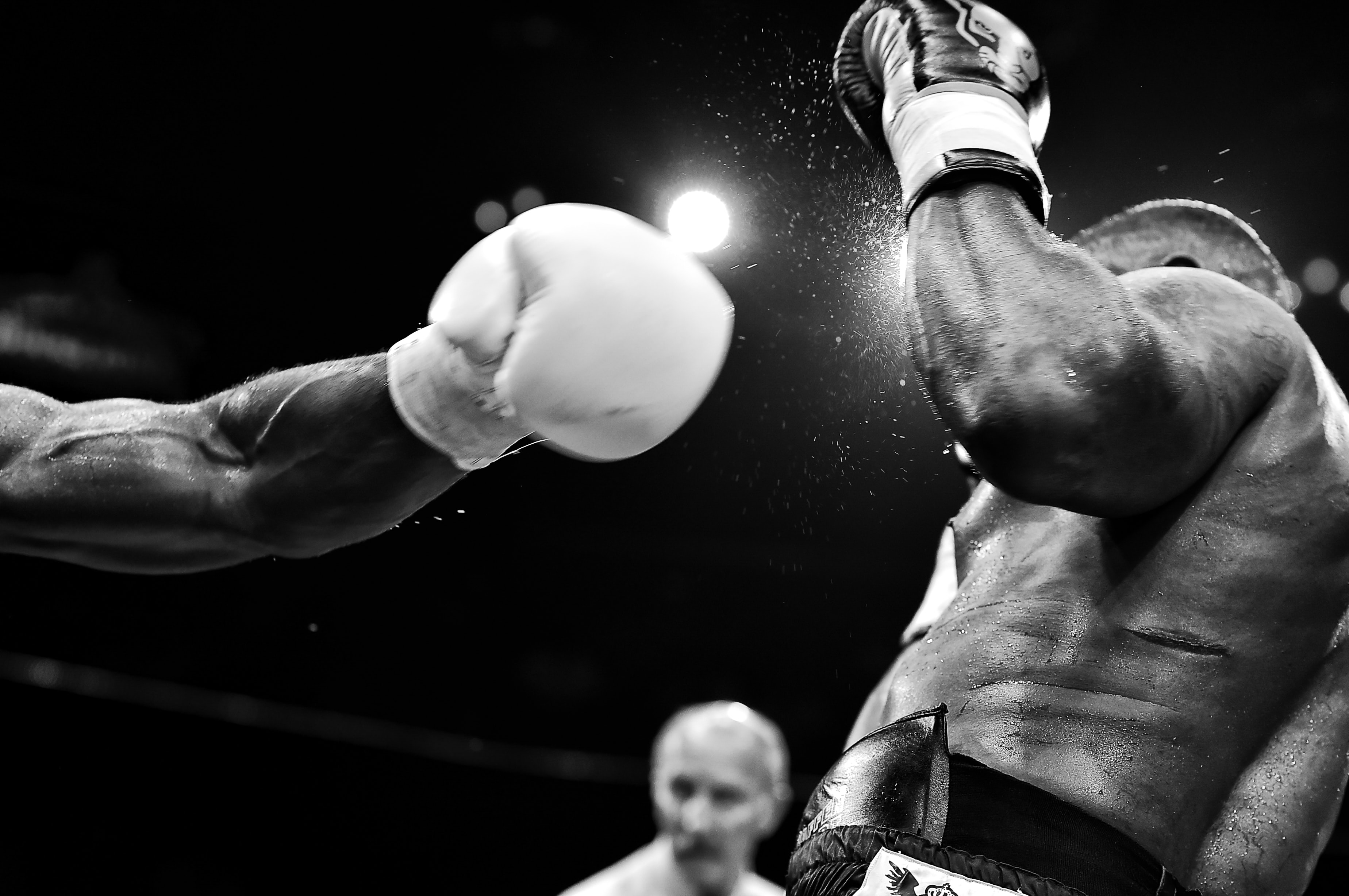 A black and white photo of a man being punched in the face in a boxing match.