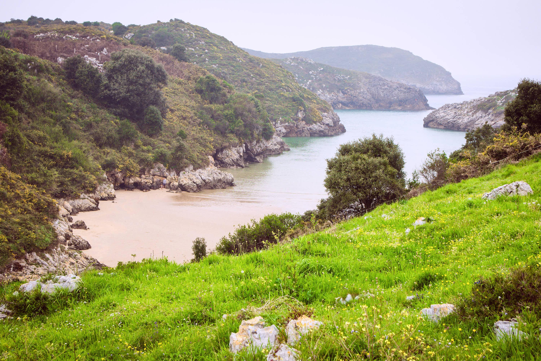 Vista de una cala lateral de la Playa de Poo con marea alta en Llanes, Asturias