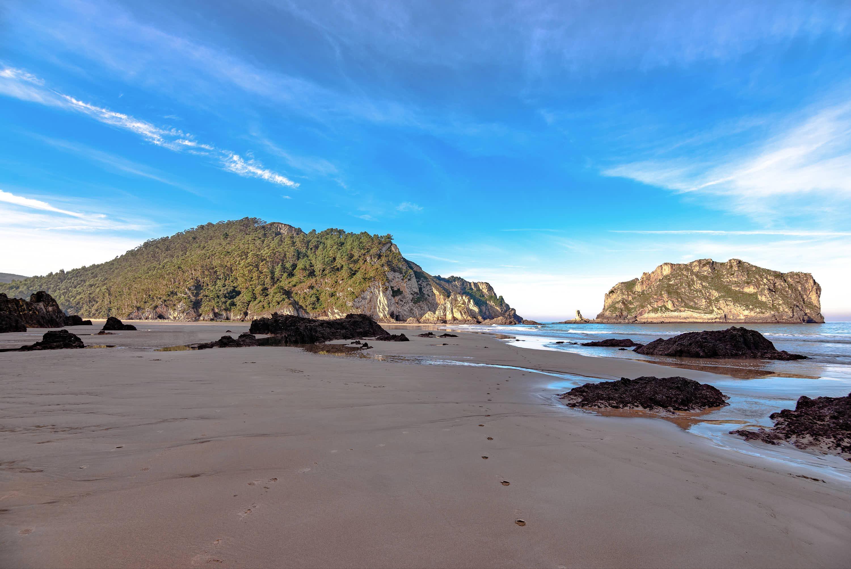 Vista desde la orilla de la Playa de La Franca con marea baja en Llanes, Asturias