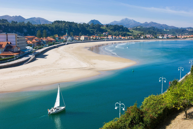 Vista superior de la Playa de Santa Marina con barco navegando por el rio Sella en Ribadesella, Asturias