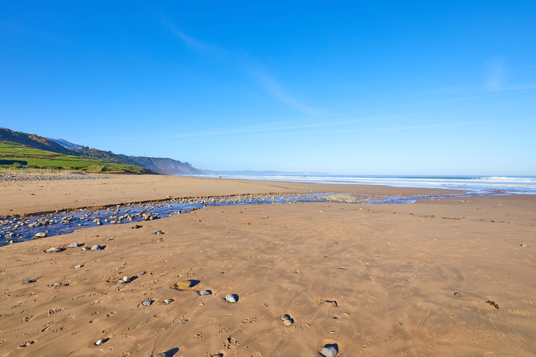 Rio cruza la arena en Playa de Vega en Ribadesella, Asturias