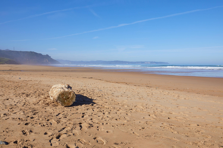 Tronco de madera sobre la arena de la Playa de Vega y el Mar Cantábrico en Ribadesella, Asturias
