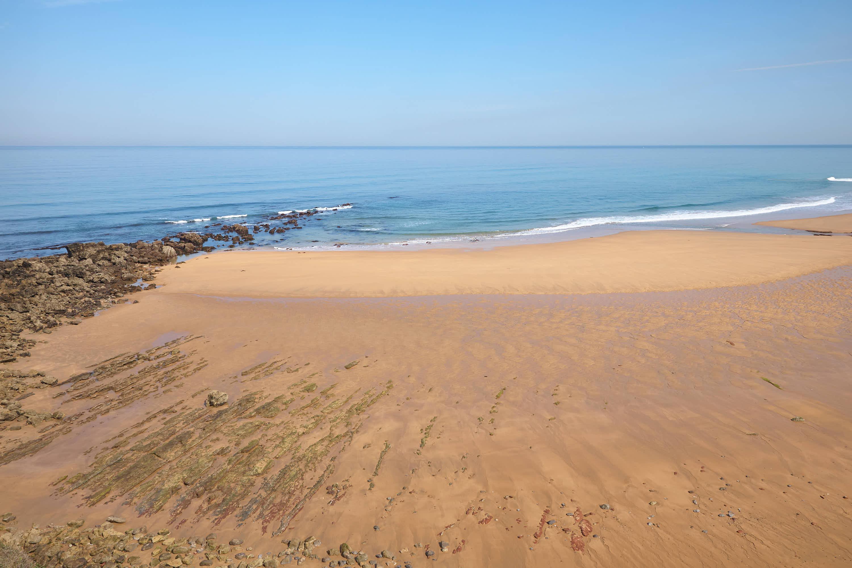 Vista del Mar Cantábrico y parte occidental de la Playa Arenal de Moris en Caravia, Asturias, con marea baja