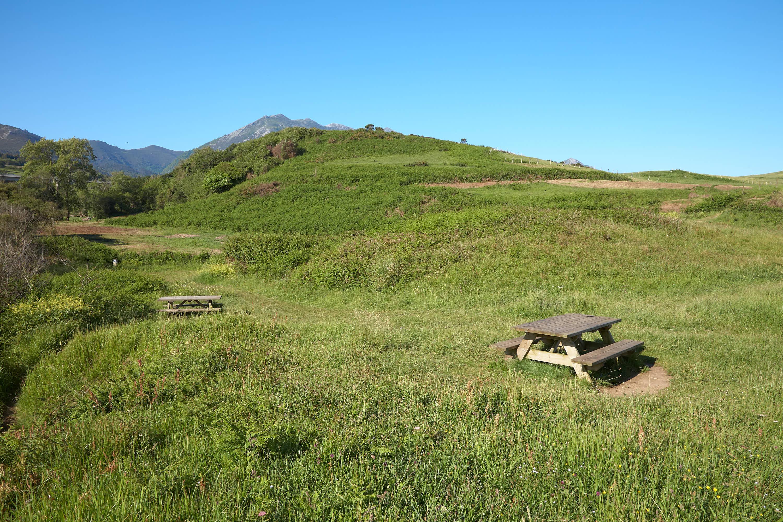 Vista de bancos sobre la hierba en el area recreativa junto a la Playa de Beciella en Caravia, Asturias