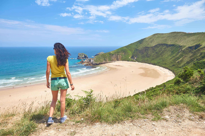 Mujer mirando la playa de Torimbia en Llanes, Asturias