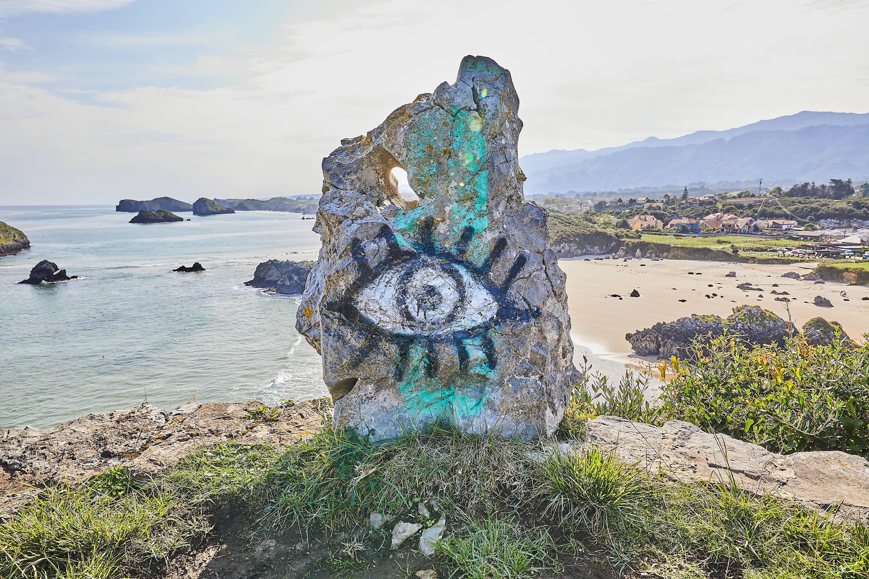 Roca con ojo pintado en el Mirador de Borizo, con la playa detrás, en Celorio, Llanes, Asturias