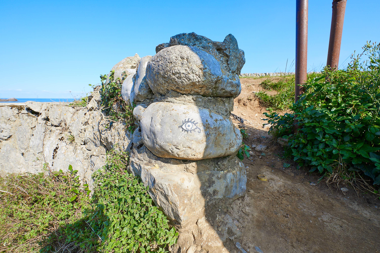 Acceso a Playa Tayada y el Mirador de Borizo, con ojo pintado en roca, en Celorio, Llanes, Asturias