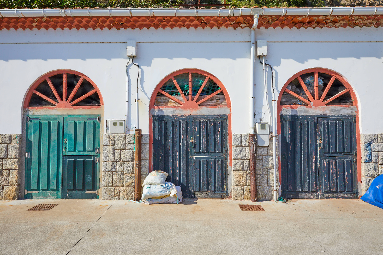 Puertas de los almacenes de pescadores en el puerto de Tazones, Villaviciosa, Asturias