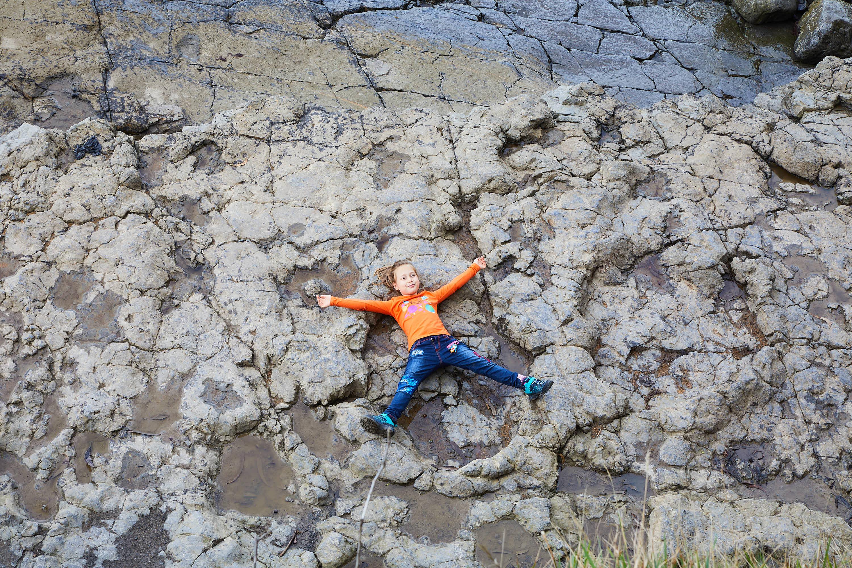 Niña tumbada sobre una huella gigante de dinosaurio saurópodo del yacimiento de icnitas de la Playa de La Griega, Colunga, Asturias