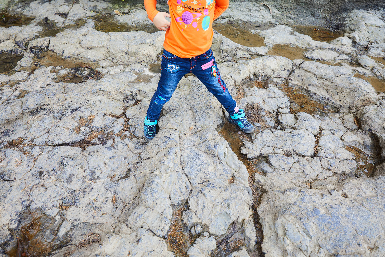 Niña pisando huellas de dinosaurio saurópodo gigantes del yacimiento de icnitas de la Playa de La Griega, Colunga, Asturias