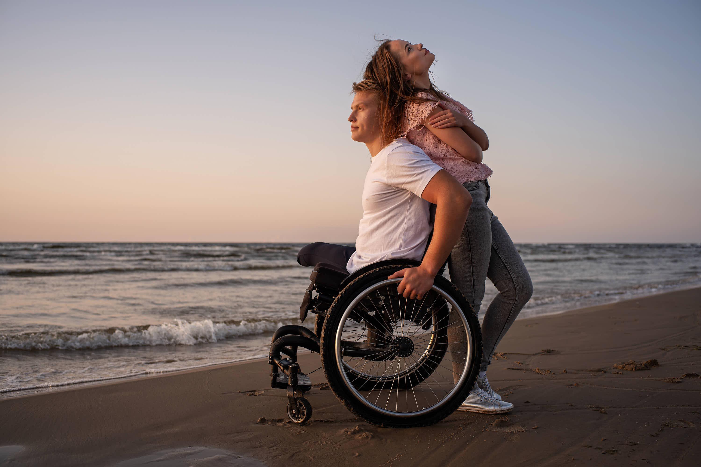 Hombre en silla de ruedas con su mujer en la playa