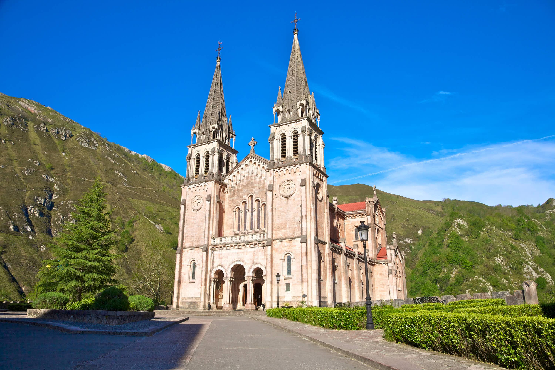 Calle de acceso a la fachada y entrada de la Basilica de Santa Maria La Real del Santuario de Covadonga, con montañas detras, en Cangas de Onis, Asturias