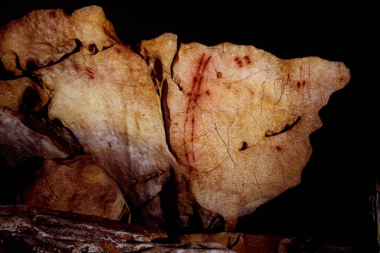 Bloque con signos rojos de la Cueva de Tito Bustillo en Ribadesella, Asturias