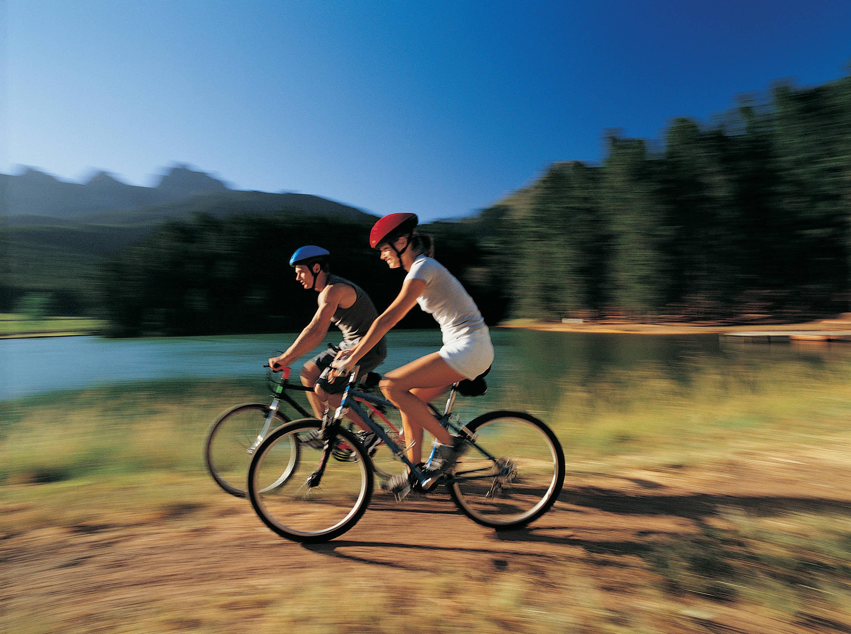 Pareja montando en bicicleta de montaña cerca de un lago