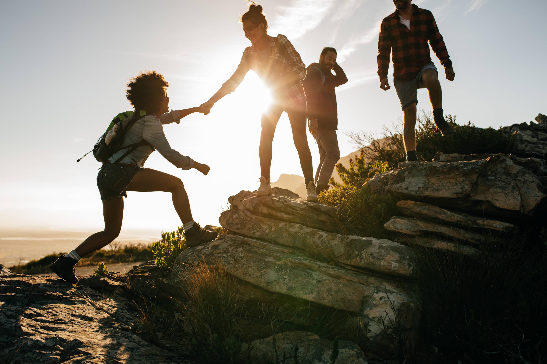 Grupo de personas activas subiendo una montaña en equipo